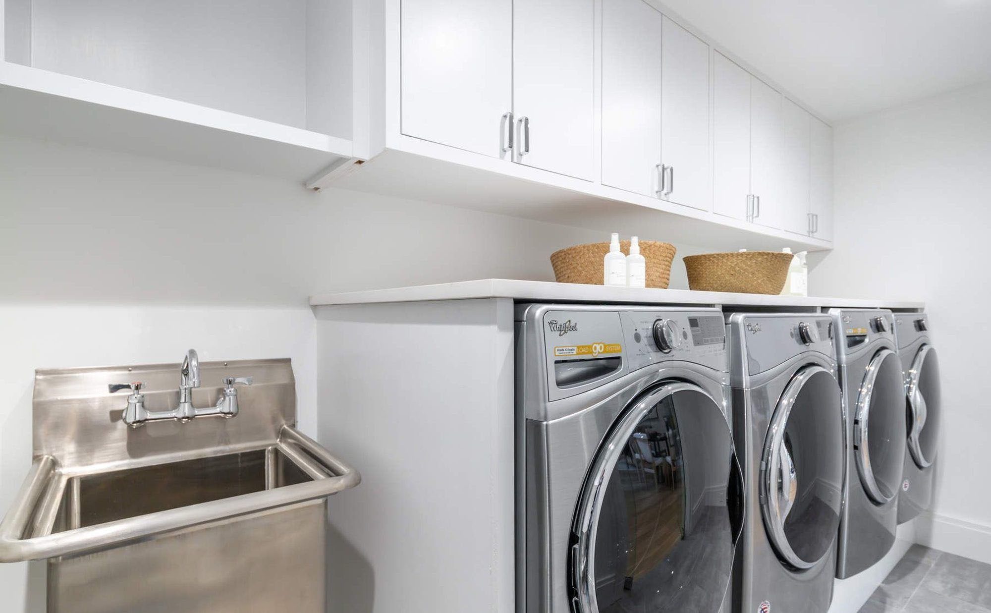 Large laundry room with two washers/dryers and a stainless steel slop sink.