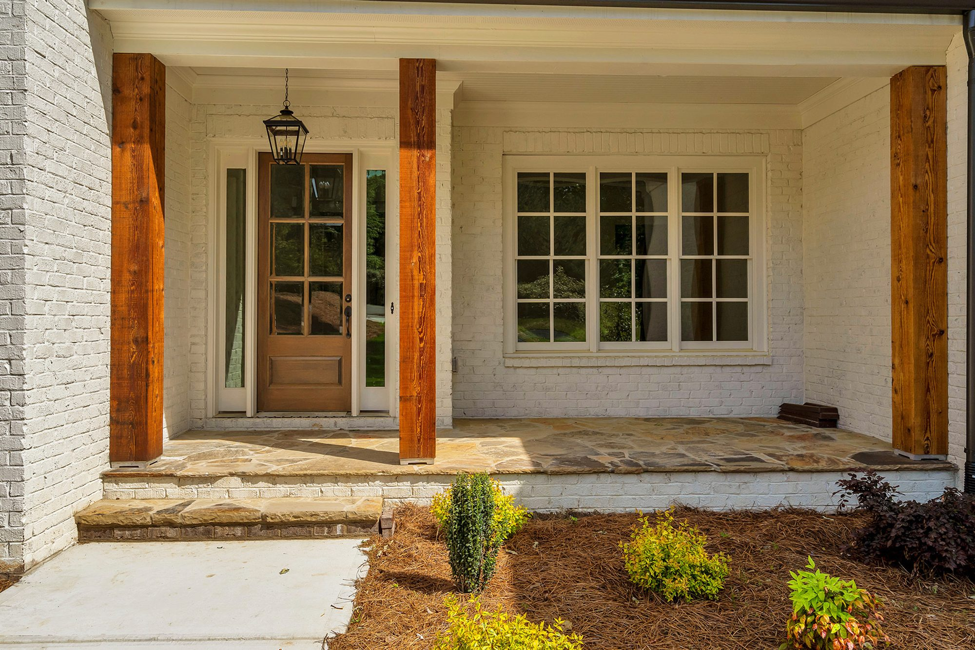 Country style front porch with painted brick walls, stone floors and real timber posts.