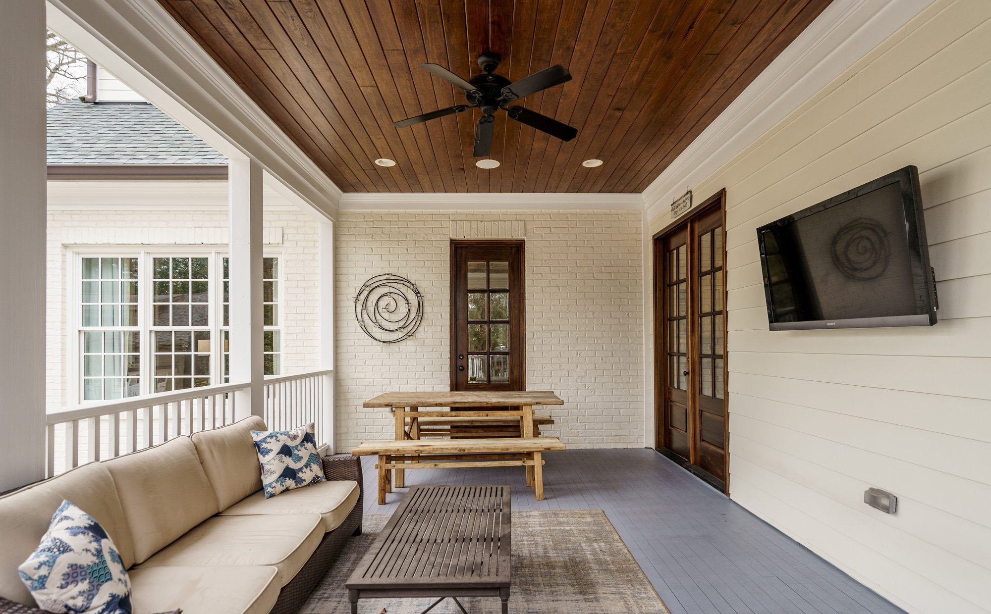 rear covered porch with painted white brick, grey decking and a wood ceiling.