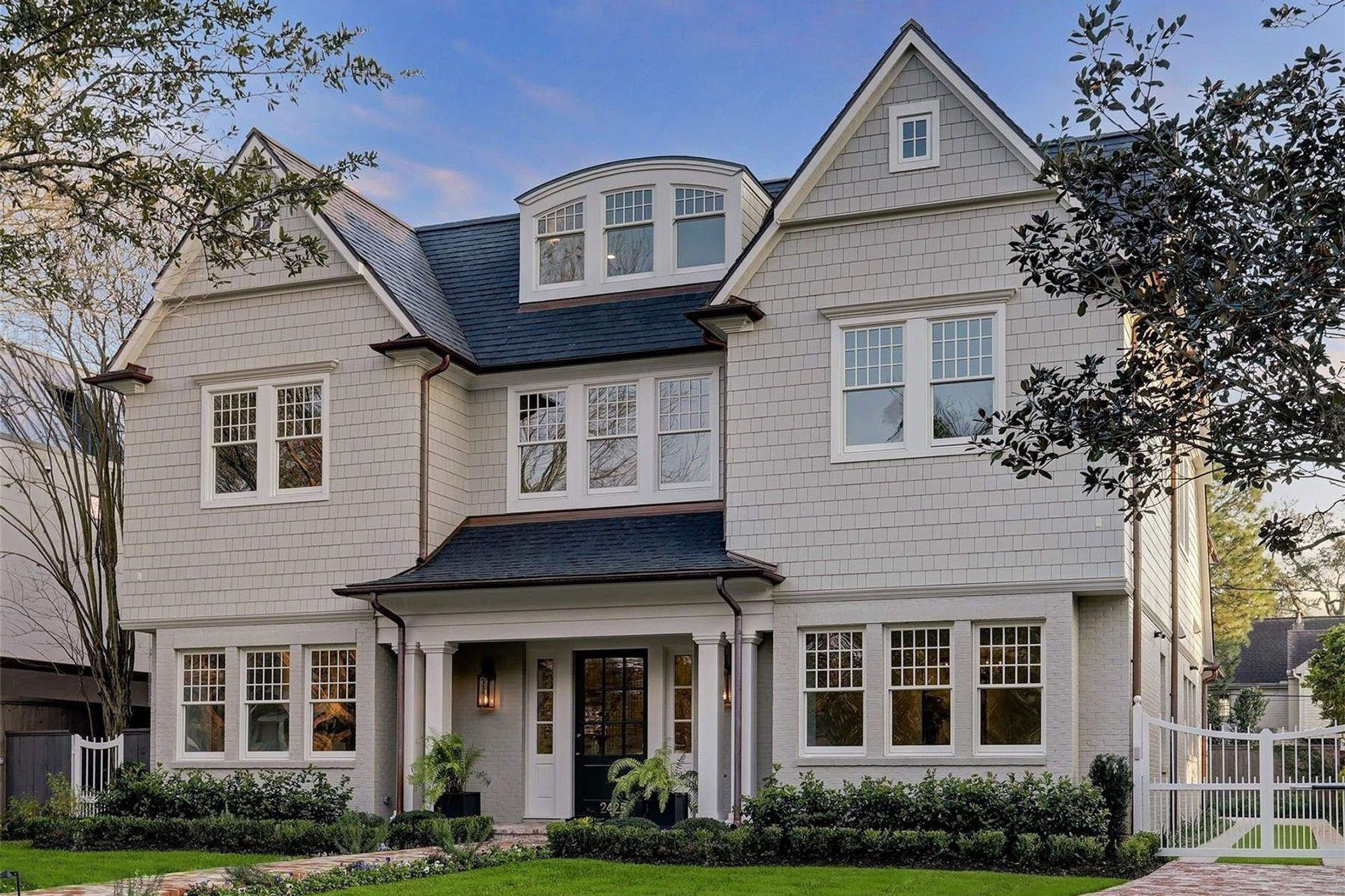 Shingle style home with a shed style portico supported by four square columns.