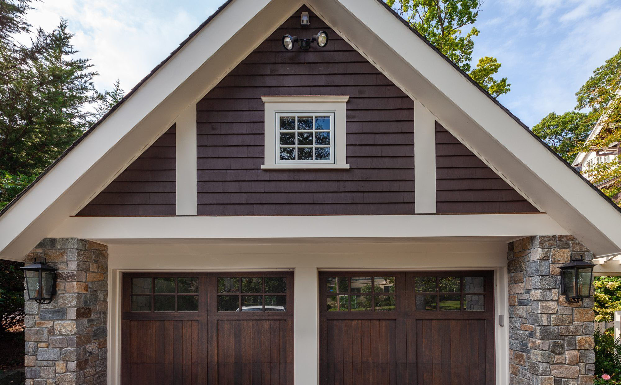 Real wood garage doors stained dark brown. Stone siding with stained wood cedar shake. buying garage doors.