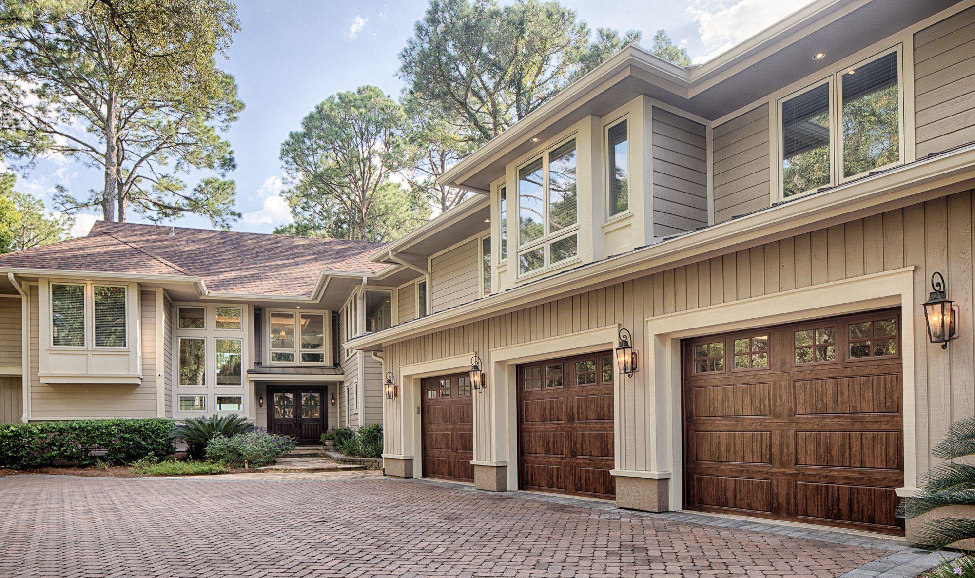Wood look garage doors with a medium brown finish. Vertical taupe siding and cream trim. buying garage doors.