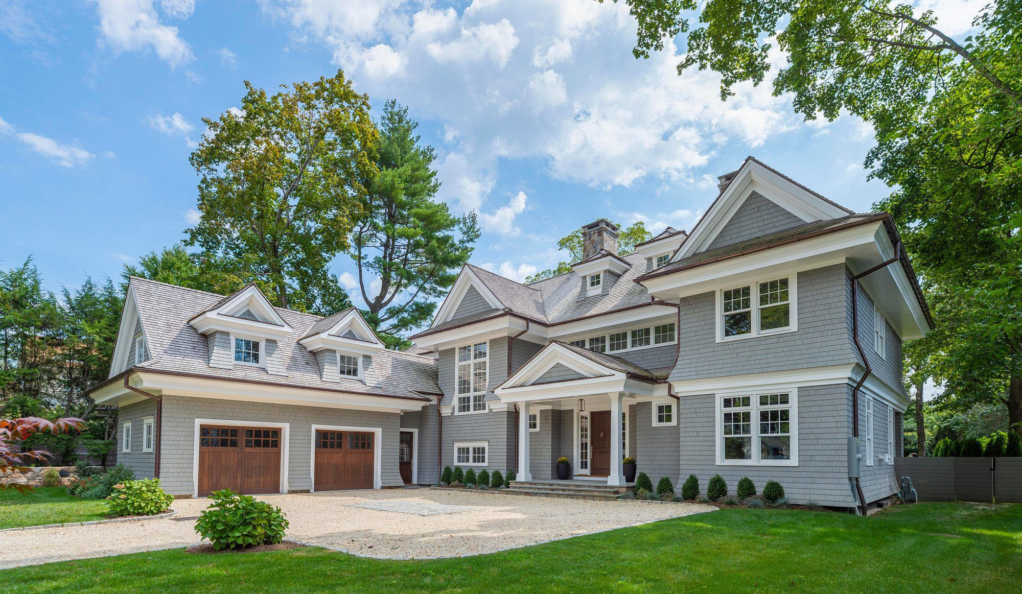 Beautiful home featuring real wood garage doors and a matching front door stained medium brown. buying garage doors.