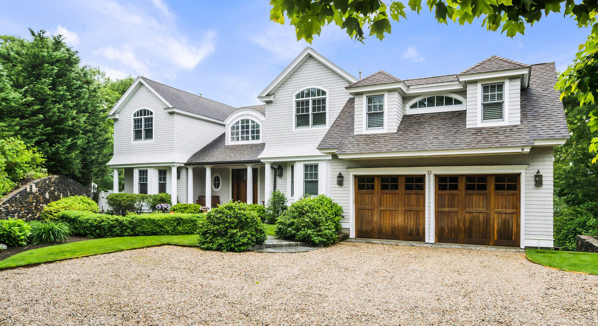Light grey home with real wood garage doors stained medium brown.