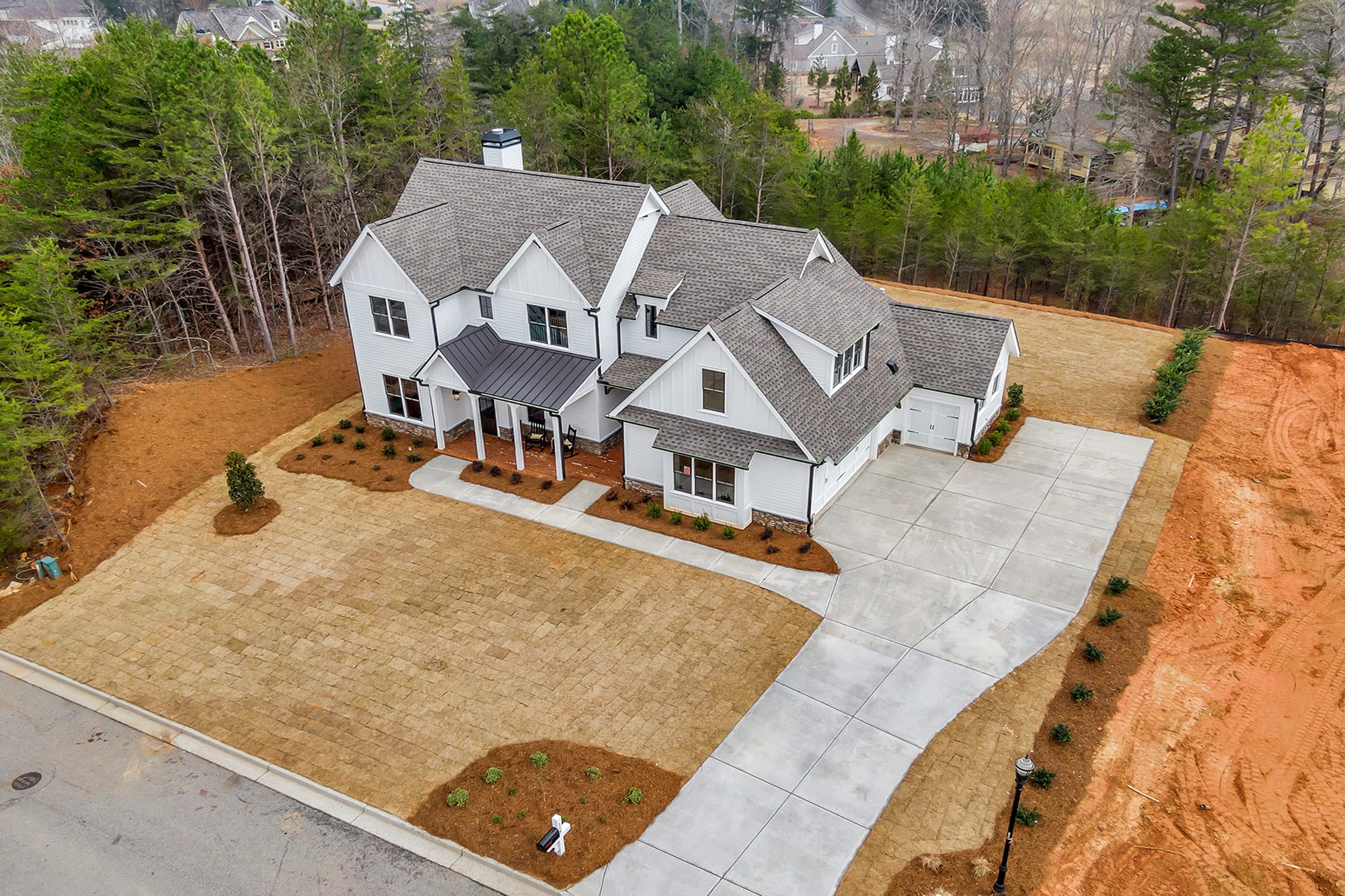 Ariel view of a beautiful Modern Farmhouse style new home featuring a white and black color scheme.