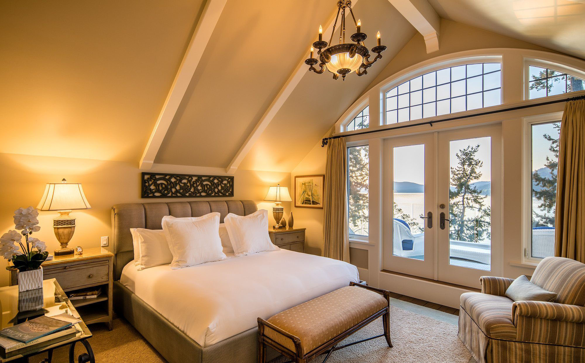 Master bedroom with vaulted ceilings finished with drywall and white beams. huge arched window and transom.