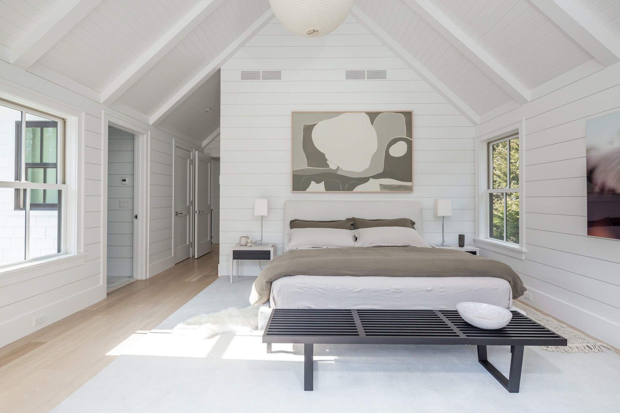 Modern farmhouse bedroom with vaulted ceilings finished with shiplap.