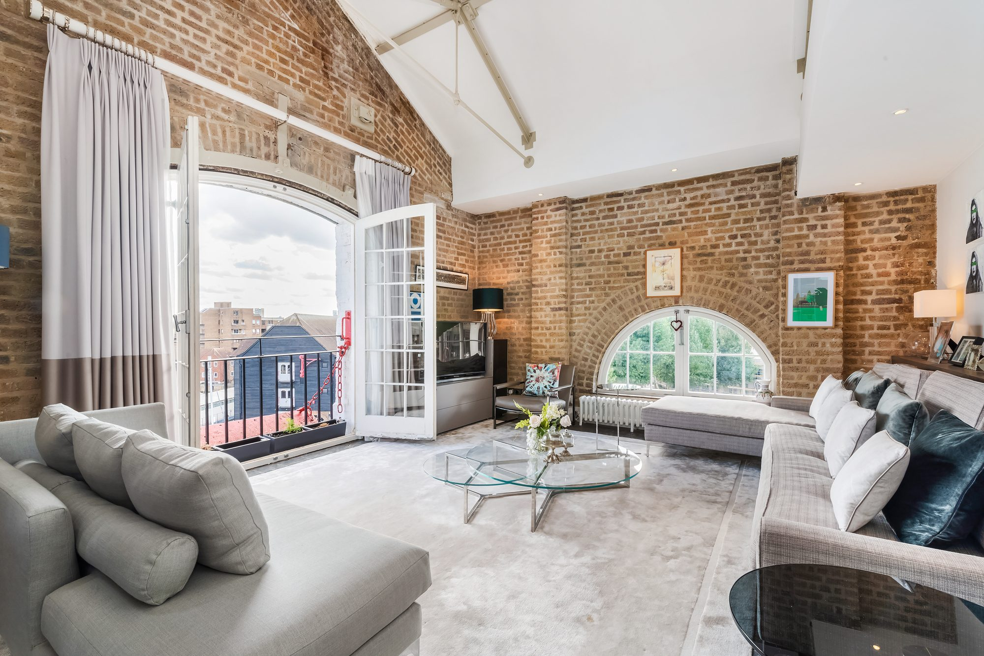 City home with brick walls and a vaulted ceiling.
