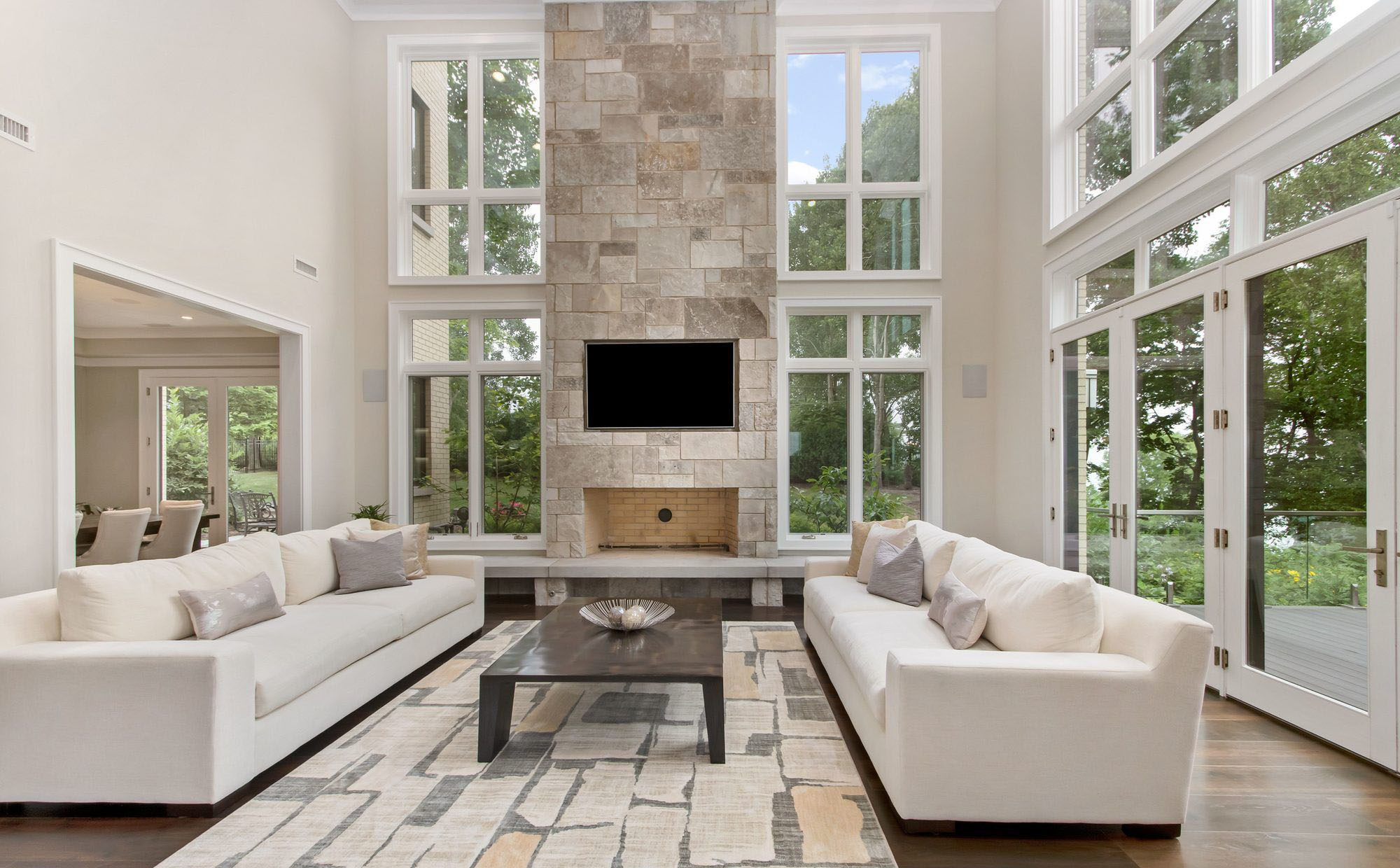beautiful modern living room with a vaulted ceiling and walls of glass. Wood burning fireplace with stone surround.