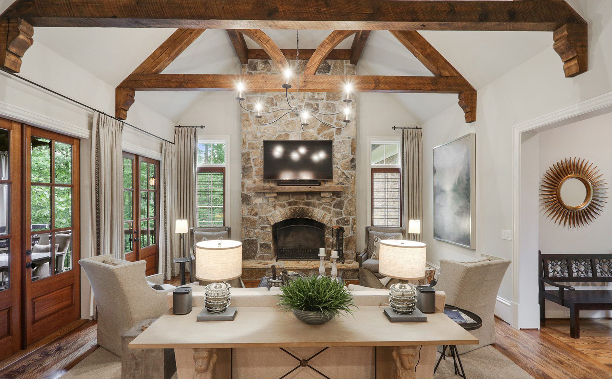 living room with vaulted ceilings and exposed wood beams. wood burning stone fireplace surround. rustic style.