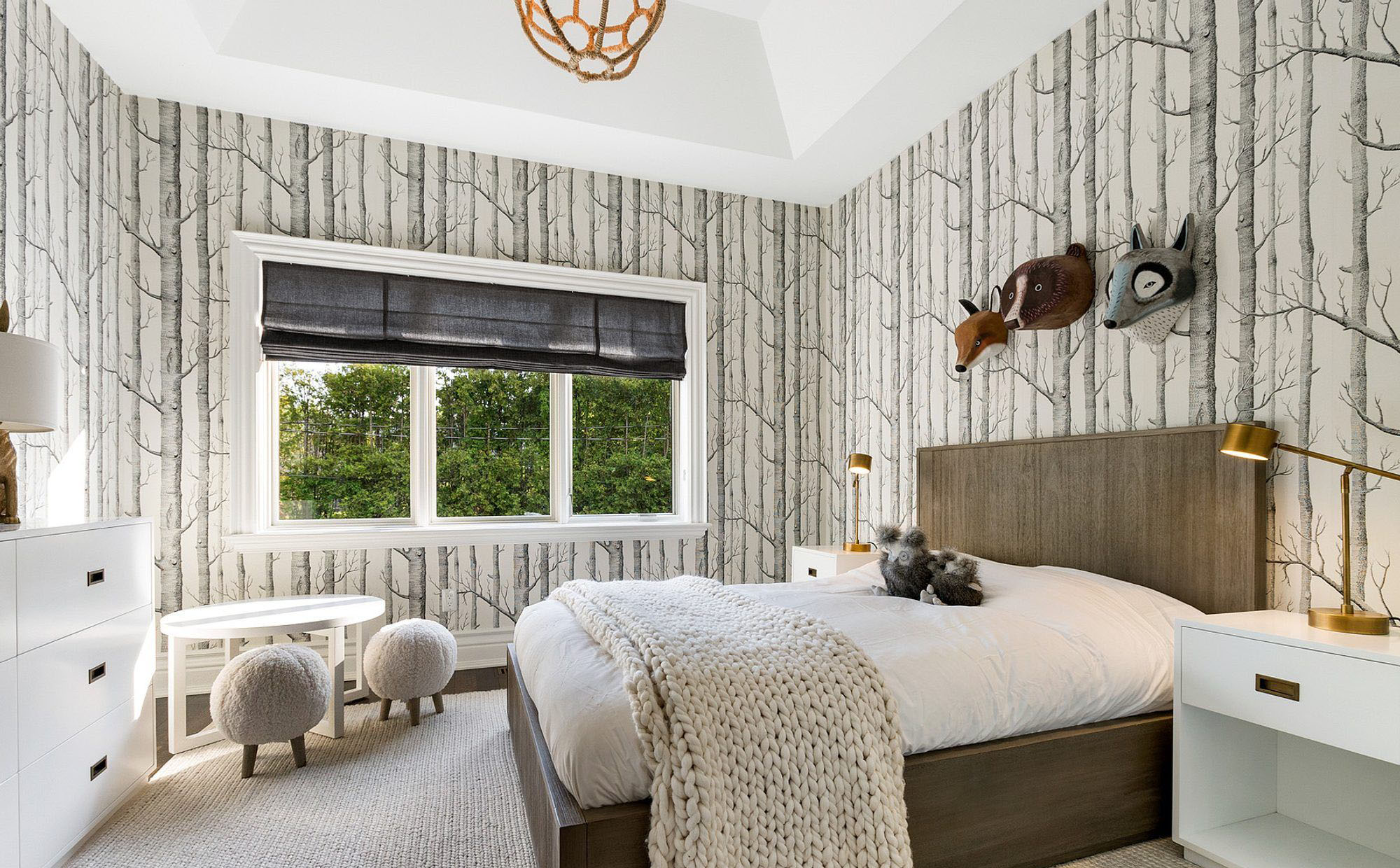 childs bedroom with grey forest wallpaper, wood bed frame and white furniture. small bedroom design ideas.