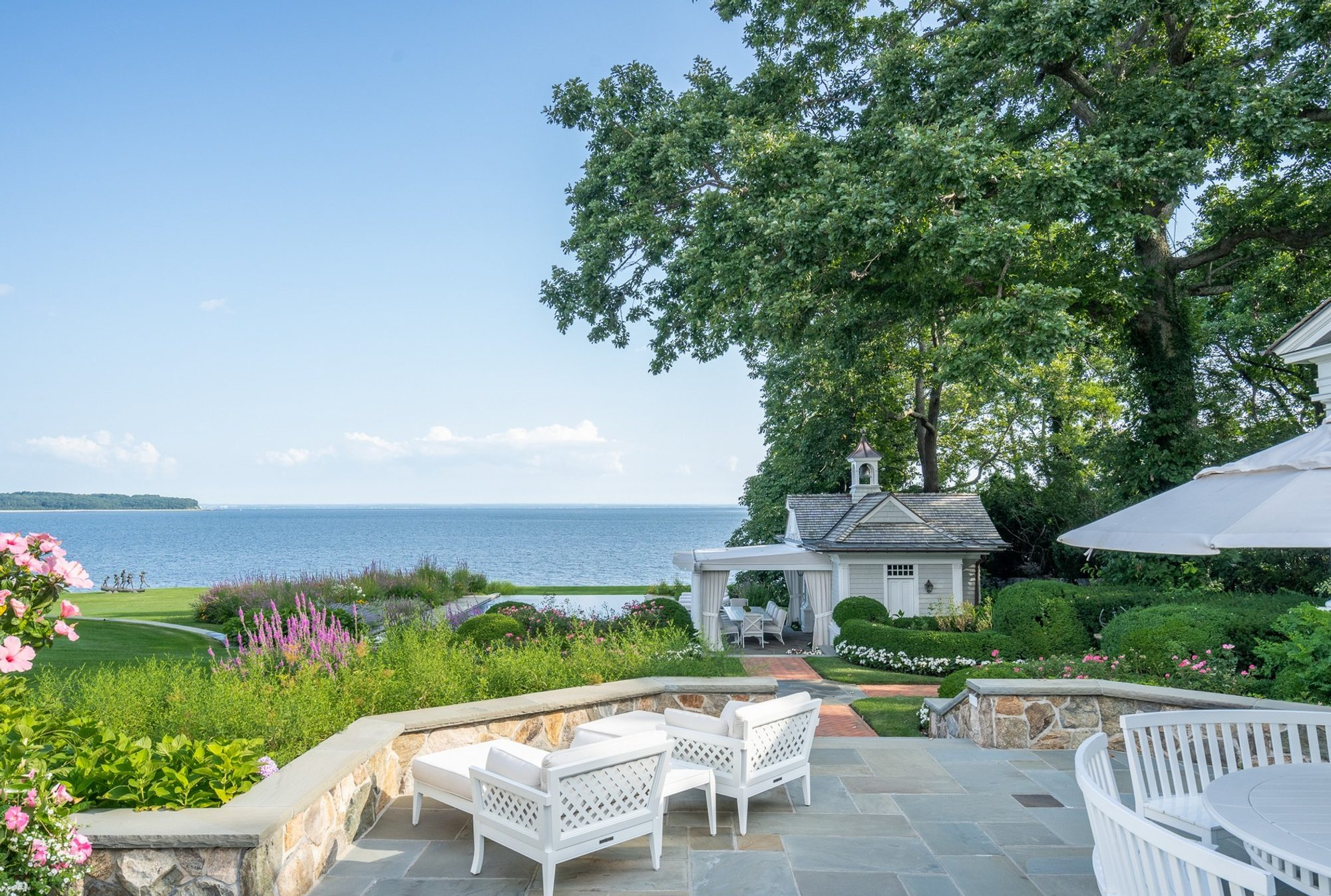 Waterfront bluestone patio with real stone retaining walls and a limestone cap.
