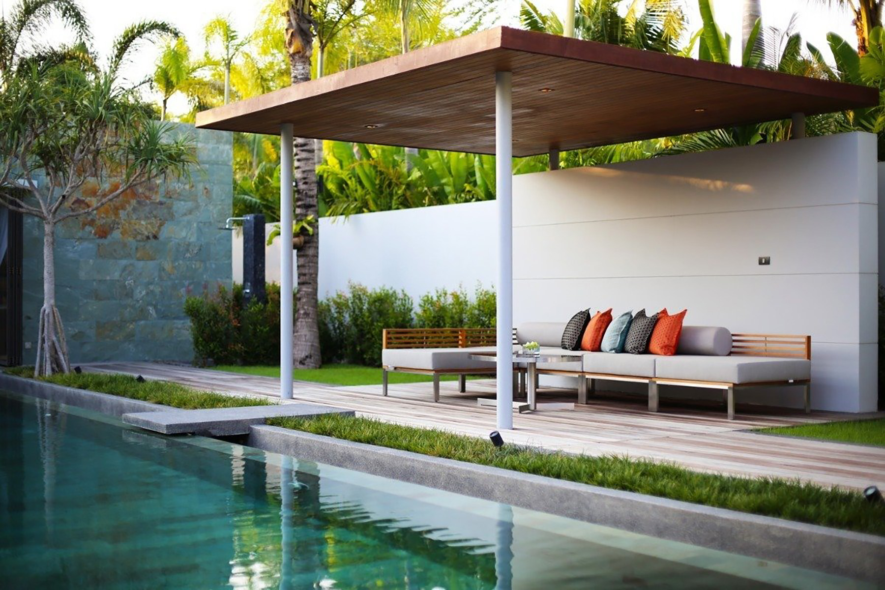 Poolside acacia wood outdoor furniture with plush cushions & pillows.