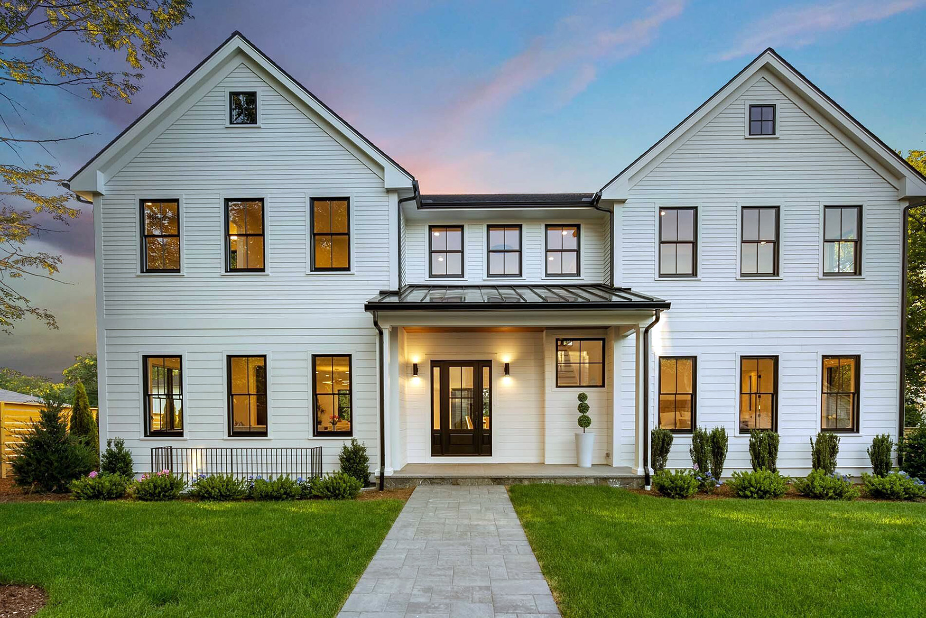 Transitional style home featuring white siding with black windows.