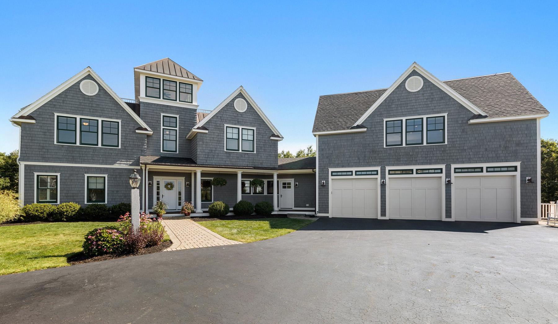 Gray cedar shake siding with white trim & black windows.