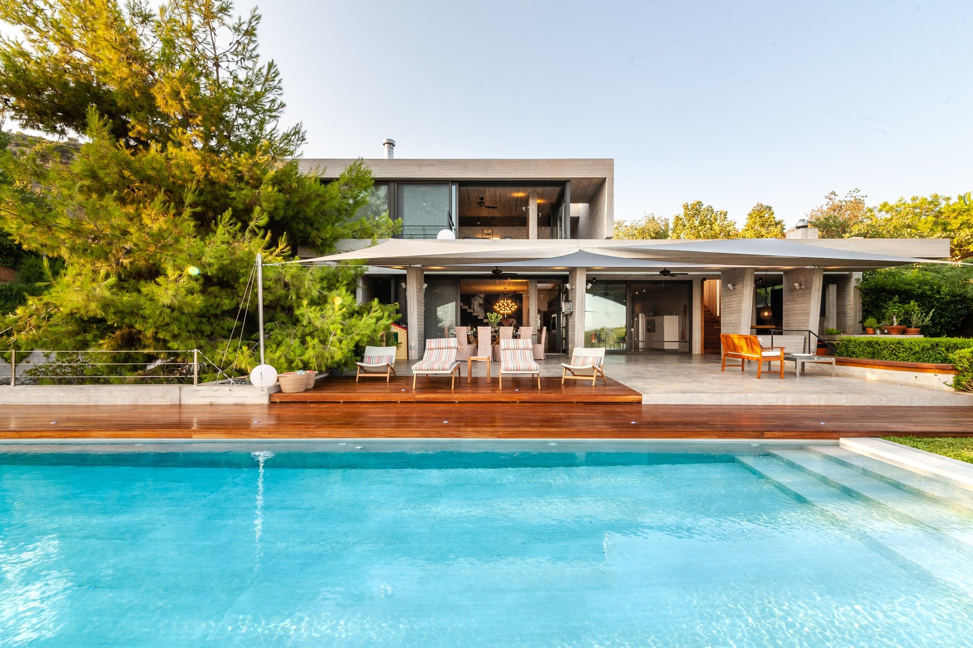 Poolside view of a Modern home with black windows and gray wood siding.