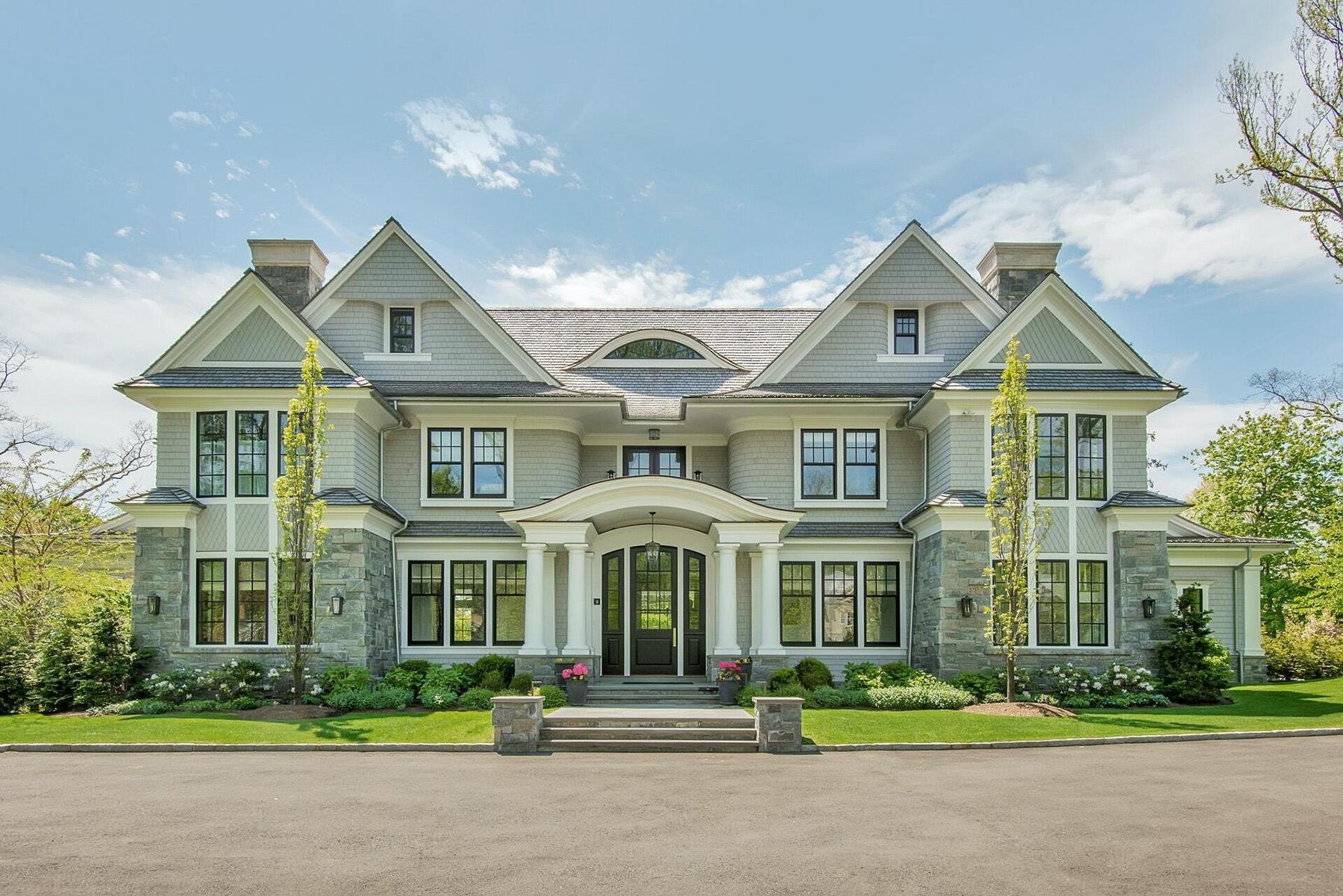 Stunning custom home with black windows, stone & gray siding.