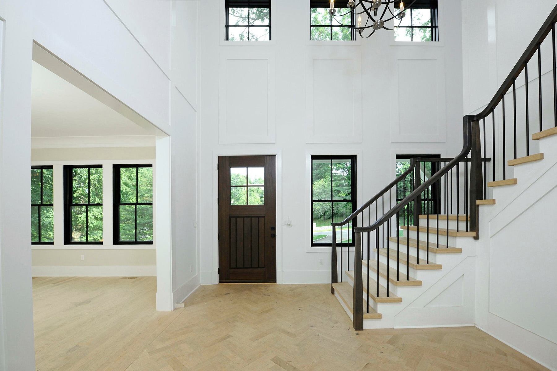 Transitional home with black windows & herringbone wood floors.
