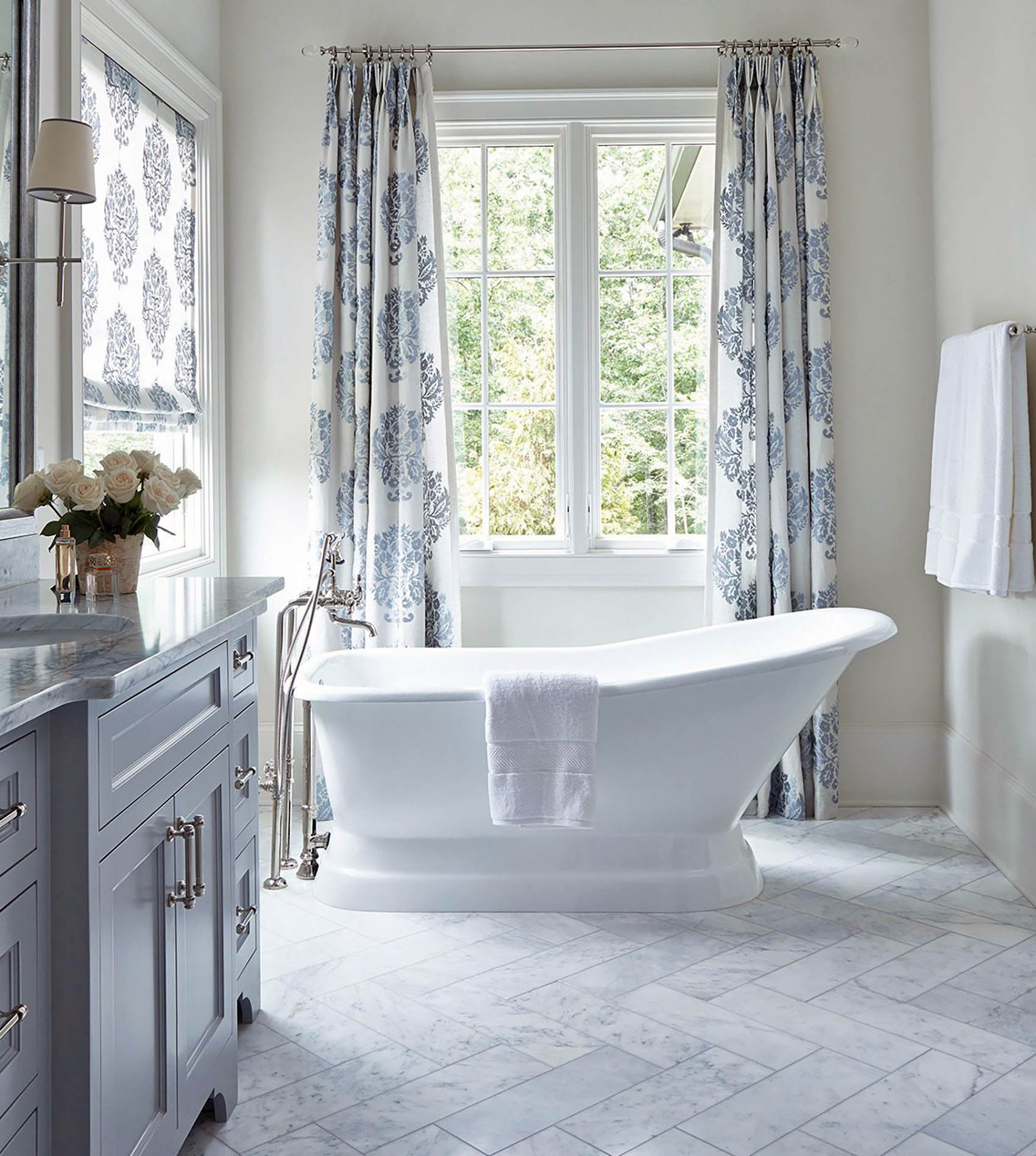 freestanding white tub with marble floors